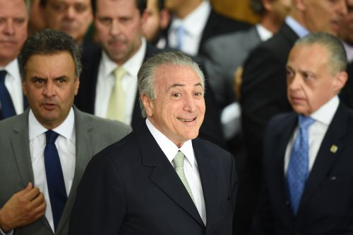 (FILES) This file photo taken on May 12, 2016 shows Brazilian acting President Michel Temer gesturing during the inauguration ceremony of the new ministers at Planalto Palace, in Brasilia. On Friday 12, 2017 Temer completes the first year of his presidential term. / AFP PHOTO / EVARISTO SA